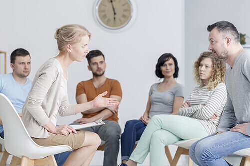 Woman explains to a group of individuals what a cognitive behavioral therapy program is